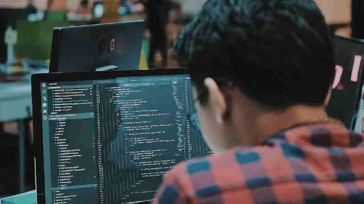 a man coding with laptop
